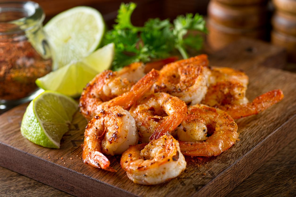 Pile of grilled cajun shrimp on wooden board with limes; Grilled Cajun Shrimp Skewers 2021 Jane Bonacci, The Heritage Cook