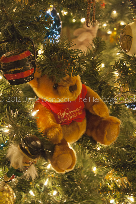 A Fairmont teddy bear tucked into the branches of one of the many Christmas trees