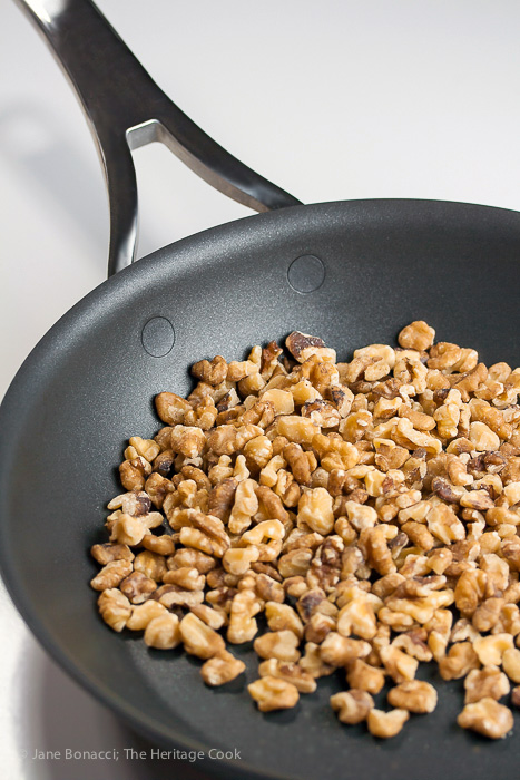 Skillet of toasted chopped walnuts, perfect accompaniment to the winter fruit salad with chocolate vinaigrette