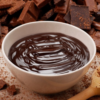 Bowl of melted chocolate with chopped chocolate and wooden spoon