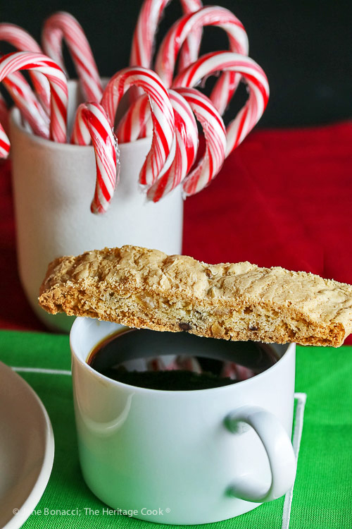 biscotti perched on top of a cup of coffee; Chocolate Chip Candied Orange Peel Biscotti © 2018 Jane Bonacci, The Heritage Cook